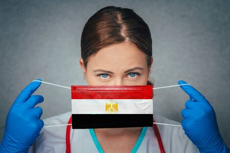 Coronavirus in Egypt Female Doctor Portrait hold protect Face surgical medical mask with Egypt National Flag. Illness, Virus Covid-19 in Egypt, concept photo