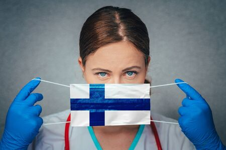 Coronavirus in Finland, Female Doctor Portrait hold protect Face surgical medical mask with Finland National Flag. Illness, Virus Covid-19 n Finland, concept photo