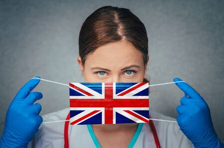 Coronavirus in United Kingdom, Great Britain, England Female Doctor Portrait hold protect Face surgical medical mask with United Kingdom National Flag. Illness, Virus Covid-19 in United Kingdom, Stock fotó