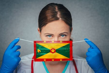 Coronavirus in Grenada Female Doctor Portrait hold protect Face surgical medical mask with Grenada National Flag. Illness, Virus Covid-19 in Grenada, concept photo