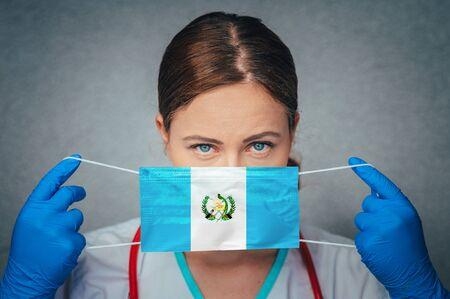 Coronavirus in Guatemala Female Doctor Portrait hold protect Face surgical medical mask with Guatemala National Flag. Illness, Virus Covid-19 in Guatemala, concept photo