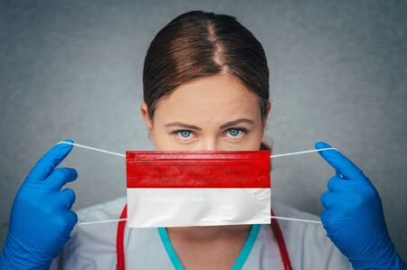 Coronavirus in Indonesia Female Doctor Portrait hold protect Face surgical medical mask with Indonesia National Flag. Illness, Virus Covid-19 in Indonesia, concept photo 版權商用圖片