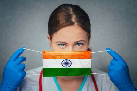 Coronavirus in India Female Doctor Portrait hold protect Face surgical medical mask with India National Flag. Illness, Virus Covid-19 in India, concept photo