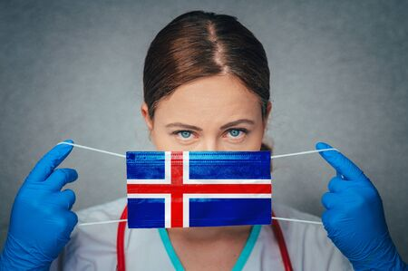 Coronavirus in Iceland Female Doctor Portrait hold protect Face surgical medical mask with Iceland National Flag. Illness, Virus Covid-19 in Iceland, concept photo