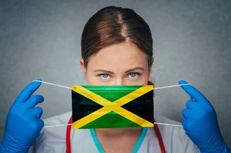Coronavirus in Jamaica Female Doctor Portrait hold protect Face surgical medical mask with Jamaica National Flag. Illness, Virus Covid-19 in Jamaica, concept photo Banque d'images