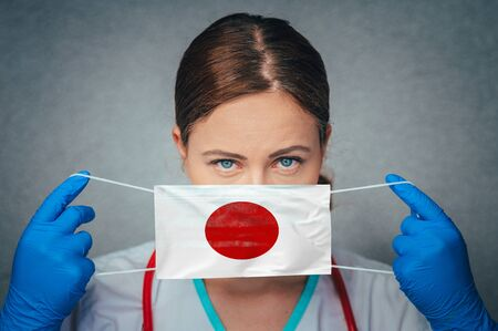 Coronavirus in Japan Female Doctor Portrait hold protect Face surgical medical mask with Japan National Flag. Illness, Virus Covid-19 in Japan, concept photo 스톡 콘텐츠