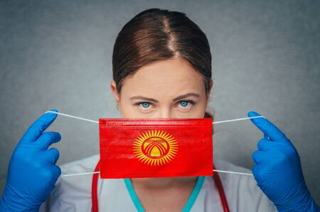 Coronavirus in Kyrgyzstan Female Doctor Portrait hold protect Face surgical medical mask with Kyrgyzstan National Flag. Illness, Virus Covid-19 in Kyrgyzstan, concept photo Stock fotó