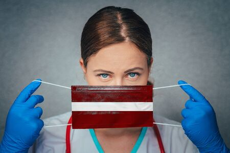 Coronavirus in Latvia Female Doctor Portrait hold protect Face surgical medical mask with Latvia National Flag. Illness, Virus Covid-19 in Latvia, concept photo