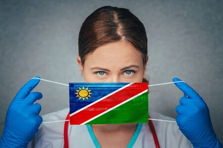 Coronavirus in Namibia Female Doctor Portrait hold protect Face surgical medical mask with Namibia National Flag. Illness, Virus Covid-19 in Namibia, concept photo