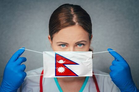 Coronavirus in Nepal Female Doctor Portrait hold protect Face surgical medical mask with Nepal National Flag. Illness, Virus Covid-19 in Nepal, concept photo Imagens