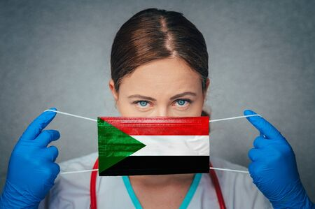 Coronavirus in Sudan Female Doctor Portrait hold protect Face surgical medical mask with Sudan National Flag. Illness, Virus Covid-19 in Sudan, concept photo