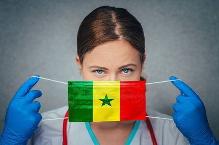 Coronavirus in Senegal Female Doctor Portrait hold protect Face surgical medical mask with Senegal National Flag. Illness, Virus Covid-19 in Senegal, concept photo