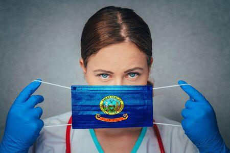 Coronavirus in U.S. State Idaho, Female Doctor Portrait, protect Face surgical medical mask with Idaho Flag. Illness, Virus Covid-19 in Idaho