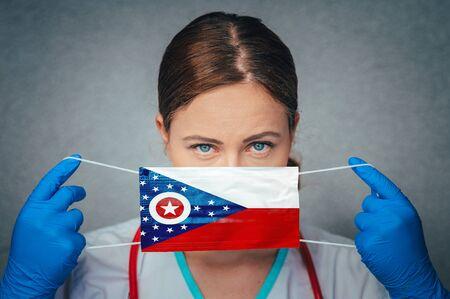 Coronavirus in U.S. State Ohio, Female Doctor Portrait, protect Face surgical medical mask with Ohio Flag. Illness, Virus Covid-19 in Ohio