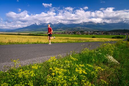 Athlete train under mountains, Morning mountains landscape in background