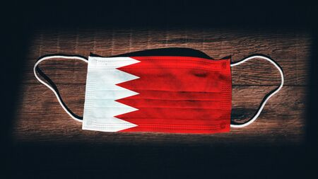 Bahrain National Flag at medical, surgical, protection mask on black wooden background. Coronavirus Covid–19, Prevent infection, illness or flu concept photo. State of Emergency, Lockdown...