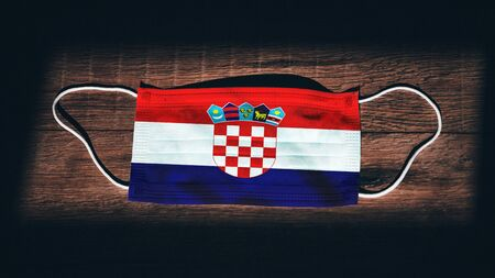 Croatia National Flag at medical, surgical, protection mask on black wooden background. Coronavirus Covid–19, Prevent infection, illness or flu. State of Emergency, Lockdown...