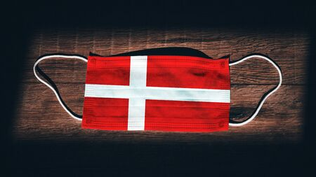 Denmark National Flag at medical, surgical, protection mask on black wooden background. Coronavirus Covid–19, Prevent infection, illness or flu. State of Emergency, Lockdown...