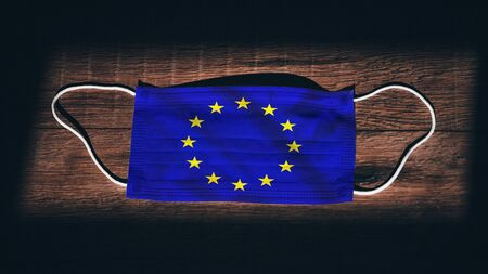 European Union, EU National Flag at medical, surgical, protection mask on black wooden background. Coronavirus Covid–19, Prevent infection, illness or flu. State of Emergency, Lockdown...