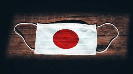 Japan National Flag at medical, surgical, protection mask on black wooden background. Coronavirus Covid–19, Prevent infection, illness or flu. State of Emergency, Lockdown... 스톡 콘텐츠