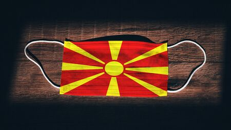 North Macedonia National Flag at medical, surgical, protection mask on black wooden background. Coronavirus Covid–19, Prevent infection, illness or flu. State of Emergency, Lockdown...