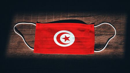 Tunisia National Flag at medical, surgical, protection mask on black wooden background. Coronavirus Covid–19, Prevent infection, illness or flu. State of Emergency, Lockdown...