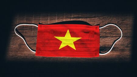 Vietnam National Flag at medical, surgical, protection mask on black wooden background. Coronavirus Covid–19, Prevent infection, illness or flu. State of Emergency, Lockdown...