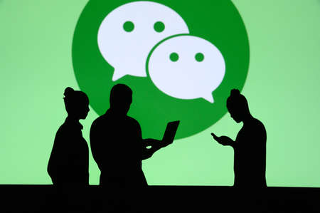 NEW YORK, USA, 25. MAY 2020: WeChat Chinese messaging, social media and mobile payment app Group of business people chat on mobile phone and laptop. Company logo on screen in background