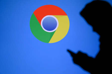 NEW YORK, USA, 25. MAY 2020: Google Chrome web browser developed by Google Young boy chat on mobile phone. Company logo on screen in background