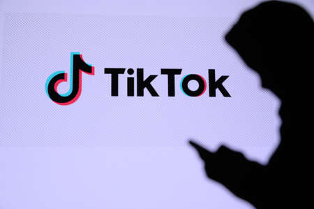 NEW YORK, USA, 25. MAY 2020: TikTok, Chinese video-sharing social networking service Young boy chat on mobile phone. Company logo on screen in background Stock Photo - 147926338