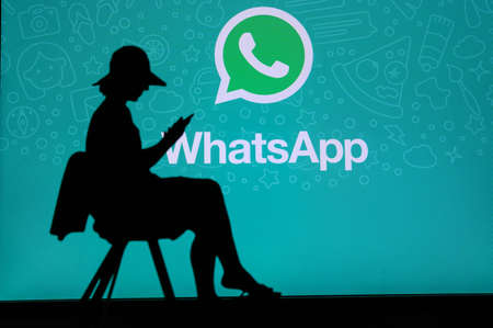 NEW YORK, USA, 25. MAY 2020: WhatsApp cross-platform messaging and Voice over service Young woman silhouette sitting on chair and playing on her smartphone. Company logo on screen in background