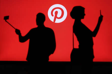 NEW YORK, USA, 25. MAY 2020: Pinterest American image sharing and social media service. Couple taking a photo on a mobile man use a selfie stick. Company logo on screen in background