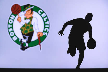 NEW YORK, USA, JUN 18, 2020: Boston Celtics basketball club logo and silhouette of young basketball player. Sport wallpaper, white edit space in background.