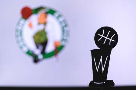 NEW YORK, USA, JUN 18, 2020: Boston Celtics Basketball club on the white screen. Silhouette of NBA trophy in foreground.