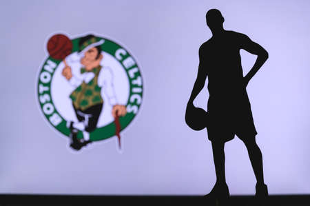 NEW YORK, USA, JUN 18, 2020: Boston Celtics logo of professional basketball club in american league. Silhouette of basket player in foreground. Sport concept photo, edit space.