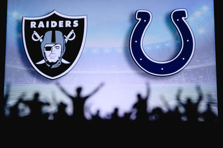 Las Vegas Raiders vs. Indianapolis Colts. Fans support on NFL Game. Silhouette of supporters, big screen with two rivals in background.