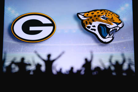 Green Bay Packers vs. Jacksonville Jaguars. Fans support on NFL Game. Silhouette of supporters, big screen with two rivals in background.