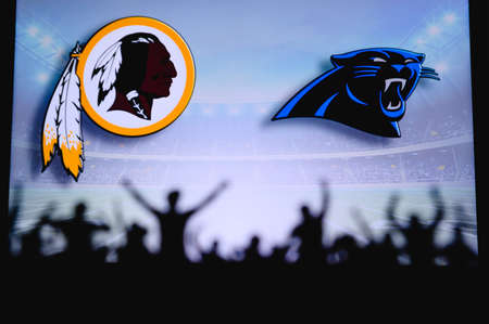 Washington Redskins vs. Carolina Panthers. Fans support on NFL Game. Silhouette of supporters, big screen with two rivals in background.