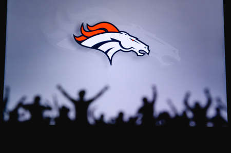 Denver Broncos. Fans support professional team of American National Foorball League. Silhouette of supporters in foreground. Logo on the big screen.