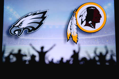 Philadelphia Eagles vs. Washington Redskins. Fans support on NFL Game. Silhouette of supporters, big screen with two rivals in background. Editorial