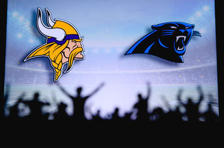 Minnesota Vikings vs. Carolina Panthers. Fans support on NFL Game. Silhouette of supporters, big screen with two rivals in background. Editorial