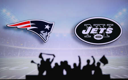 New England Patriots vs. New York Jets. Fans support on NFL Game. Silhouette of supporters, big screen with two rivals in background.