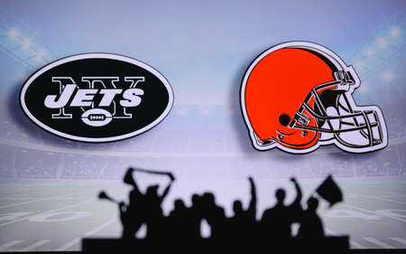New York Jets vs. Cleveland Browns. Fans support on NFL Game. Silhouette of supporters, big screen with two rivals in background.