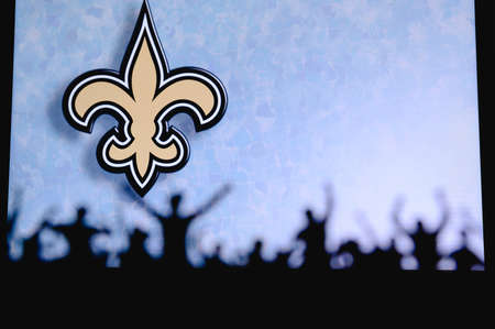 New Orleans Saints. Fans support professional team of American National Foorball League. Silhouette of supporters in foreground. Logo on the big screen.