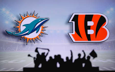 Miami Dolphins vs. Cincinnati Bengals. Fans support on NFL Game. Silhouette of supporters, big screen with two rivals in background.