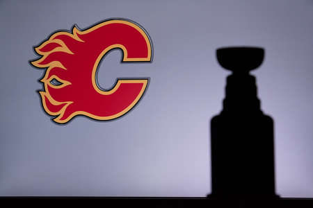 TORONTO, CANADA, JULY 17: Calgary FlamesLogo of NHL club on the screen. Stenley Cup Trophy Silhouette.