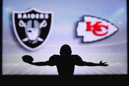 Las Vegas Raiders Vs. Kansas City Chiefs. NFL Game. American Football League match. Silhouette of professional player celebrate touch down. Screen in background.