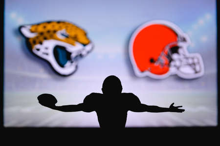 Jacksonville Jaguars Cleveland Browns. NFL Game. American Football League match. Silhouette of professional player celebrate touch down. Screen in background.
