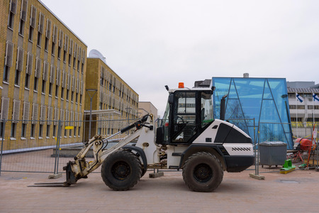 tractor manipulator stands in the city near the construction site.