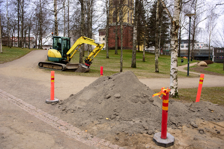 Mini excavator at a construction site. The excavator stands near the dug hole